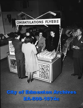Women handing out souvenirs from the Edmonton Flyers Hockey team.