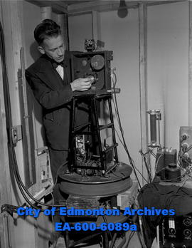 Dr. D.B. Scott at the U of A demonstrates instrument that shows activity of radioactive atom part...