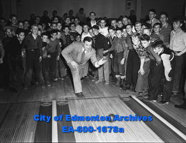 Edmonton Bulletin carriers' Bowling League; group of boys watch publisher H.L. Straight bowling t...