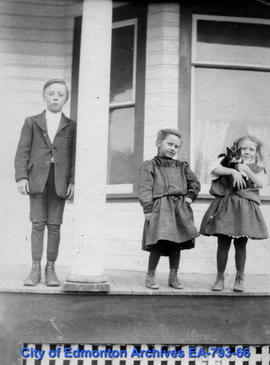 Three children with cat on porch