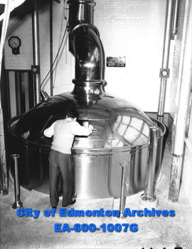 Northwest Breweries: man examining the brew in a big kettle pot.