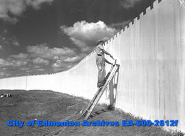 """Exhibition Grounds Get Face Lifting For Fair"". Painting the fence."