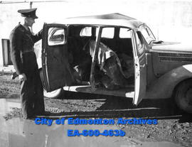 Constable L. B. Nicholson examines the side of a car which has been hit by a truck.