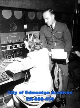Terry McPeake, radio operator, and Squadron Leader R. D. Hansen establish radio contact with RCAF...