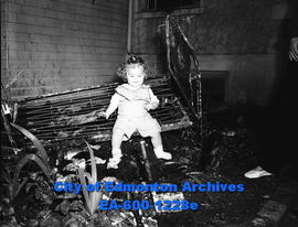Barbara Nilles sitting on burnt crib after house fire.