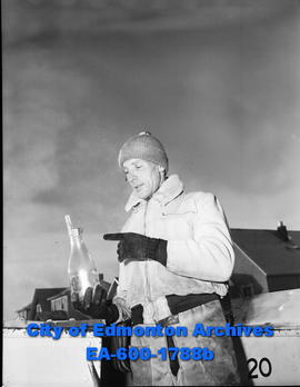 Milkman, Doug Overton, heats bottles to get money out that is frozen in the bottle.