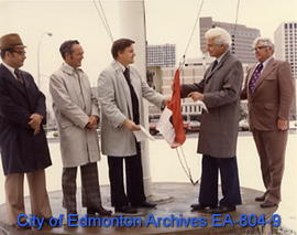 Mayor Ivor Dent (second from right) raising the special RCMP Centennial Flag at City Hall