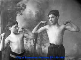 Two boys showing their muscles at a photograph studio.