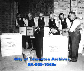 Rotary Club members packing boxes of canned meats for shipment to Edmonton, England: (L-R) Sid We...