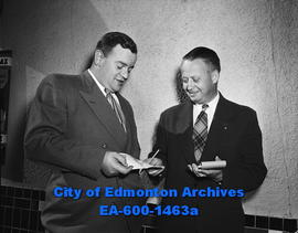 Mr. H.L. Straight, publisher of the Edmonton Bulletin, buys apples from Kiwanis President Walter ...