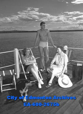 Women's Page: Wabamun Lake. L-R: Mrs. A. C. Emery, Michael Emery and Mrs. W.J.A. Mustard sit on c...