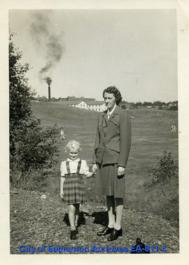 Woman and Child, field and factory in background