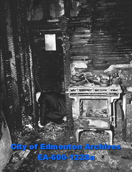 Man kneeling in burnt house.