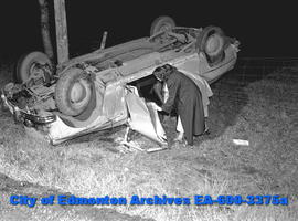 Two women inspect car accident scene.