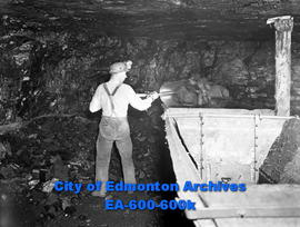 Scenes from Samis Colleries domestic coal mine: unidentified miner loads coal into a mine car.