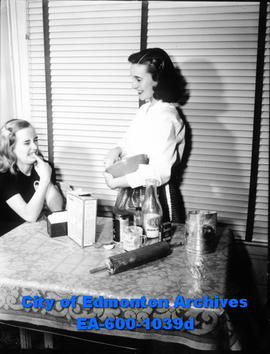 Miss Edmonton of 1948, Joan Farley, baking a cake as her sister Kay watches.