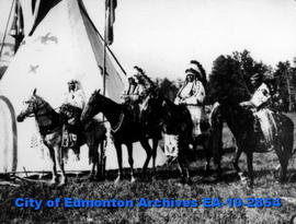 Indigenous individuals on horseback in front of a painted teepee