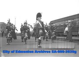 """Half-Hearted Welcome Given Touring Easterners"". Toronto Girls' Pipe Band march in parade."