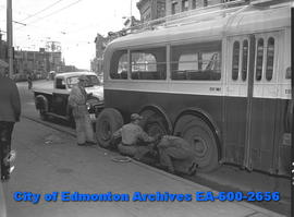 Edmonton tranist workers change tire on city bus.