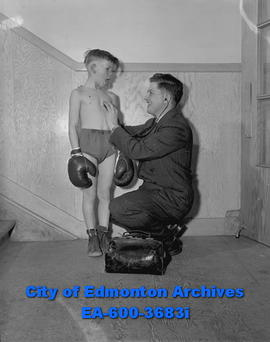 Edmonton Boys' Boxing Club member Lloyd Higginson gets a check-up from Dr. E.L. Smith.