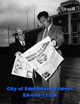 Longden reading the Edmonton Bulletin at the Municipal Airport.