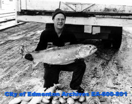 Winter fishing operations on Great Slave Lake: Carl R. Carlson holds a 43.5 pound lake trout with...