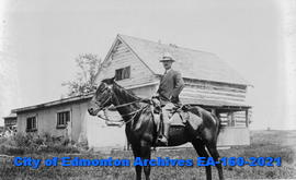 Charles Bowen on top a horse in front of a house in British Columbia.