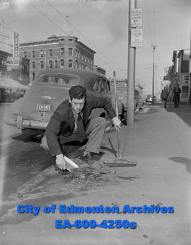 Mud feature: Stan Burke gathers mud from city sidewalk.