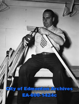 Doug Hardy, hockey coach of the Edmonton Flyers, taping stick.