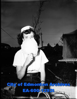A girl eating cotton candy at the Camrose Annual Fair.