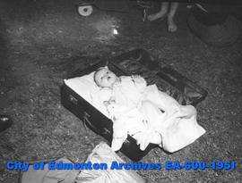 Hottest day of the year: Angeline Labelle relaxes in a suitcase in Kitchener Park.