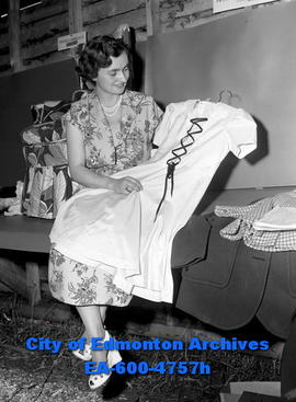 Rose Marie Fontaine inspects dress which won Mrs. Phil Charron a first prize.