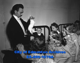City magician Walter T. Maidens gives a free show at the children's ward of the University Hospital.