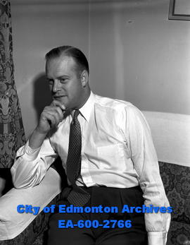 Reconstruction Minister Robert H. Winters studies provincial housing problems.