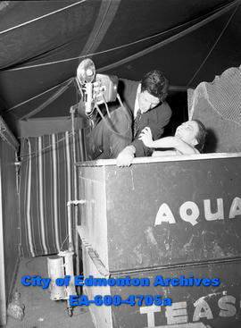 Burke, underwater interview man dressed and holding camera looking into tank in which a woman is ...