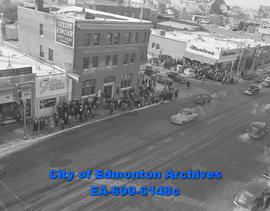 Crowd watches Santa Claus arrive by helicopter on the roof of the Hudson's Bay Company store.
