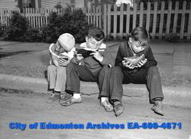 Youngsters Eddie Manilaki, Leopold Zalykey and George Holowka sit on a curb eating a watermelon.