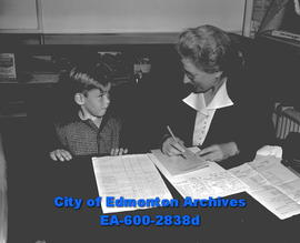 Back to School Feature. Miss B. Bruce registers Jerry Noga for grade one at Alex Tayor School