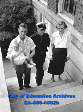 City policeman escorting Mr. and Mrs. R.E. Mille with daughter Janice, up the steps of building.